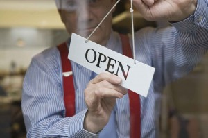 business owner holding open sign graphics